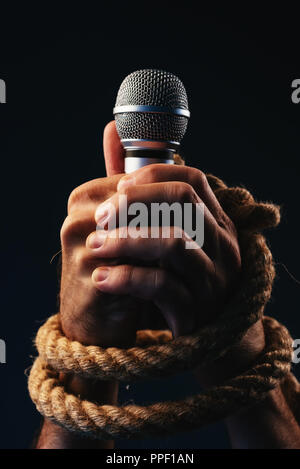 Freedom of speech, conceptual image with male person holding a microphone with hands tied in ropes, low key image