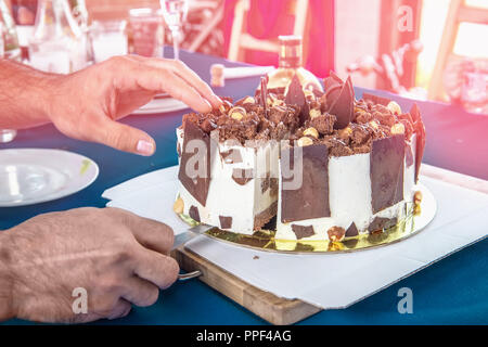 An airy piece of chocolate cake on a plate . men's hands cut the cake - Stock Photo