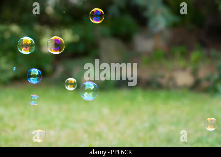Group of colorful soap bubbles at the green background in a garden - Stock Photo