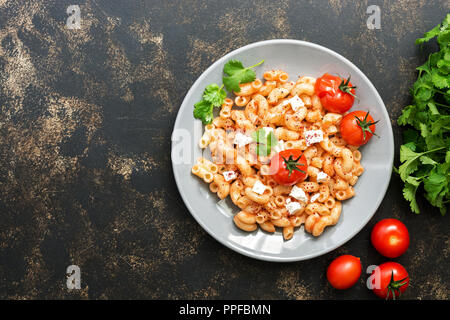 Pasta with sauce, feta cheese and baked tomatoes on a dark background. - Stock Photo