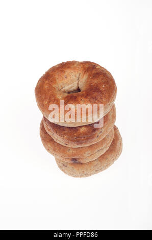Looking down at stack of multigrain bagels on white background - Stock Photo