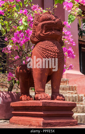 Red stone statue of a mythical guardian lion figure in the grounds of the National Museum of Cambodia, Phnom Penh, Cambodia - Stock Photo
