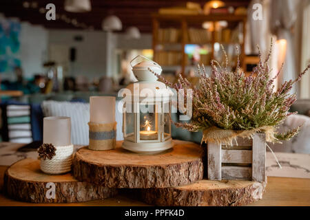 Beautiful stylish autumn table decoration .white - pink heather in autumn basket.Candles and lamps. stylish table catering.Still life details,cozy concept.Restaurant interior decor in warm and brown colors - Stock Photo