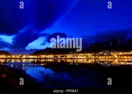 The city lights are reflected in the Beagle Channel in the blue hour, Ushuaia, Tierra del Fuego Province, Tierra del Fuego - Stock Photo
