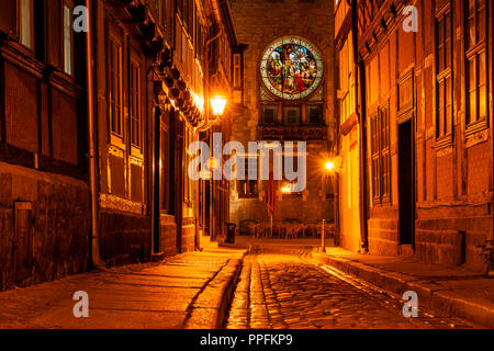 Narrow alley with half-timbered houses, behind the town hall with windows with enlightened stained glass, cobblestones - Stock Photo
