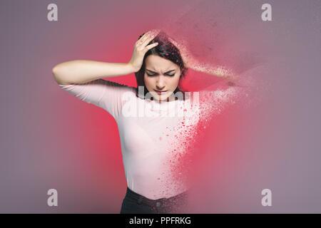 beautiful woman suffering from headache, with red splatter around - Stock Photo