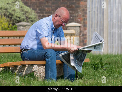 Smart casually dressed caucasian middle aged man sitting on a wooden park bench reading a newspaper in the UK. - Stock Photo