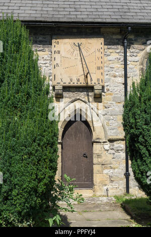 Wall mounted 18th century sundial above an entrance to St Lawrence Church, Eyam, Derbyshire, UK - Stock Photo