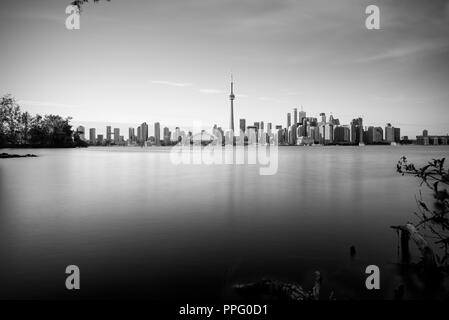 Long exposure of Toronto skyline with Lake Ontario in the foreground, as seen from Center Island. - Stock Photo