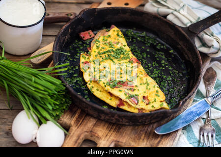 Cast iron frypan with omlette with ham and chives on old wooden background. Rustic style. - Stock Photo