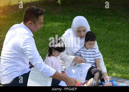 malay muslim family reading outdoor - Stock Photo