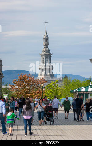 Tourists enjoying a stroll on the Dufferin Terrace. The ornamental steeple of the Camille-Roy Building (Séminaire de Québec) can be seen in the back. - Stock Photo
