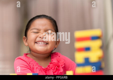 Smiling latino girl playing with colorful building blocks who is proud of her accomplishments - Stock Photo