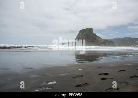 Stunning Tasman Sea waters and Lion Rock at the volcanic black sand Piha Beach in Auckland, New Zealand - Stock Photo