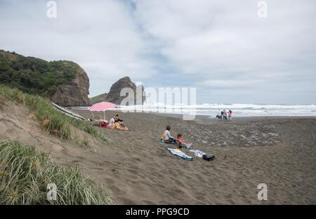 Auckland, North Island, New Zealand-December 17,2016: Tourists enjoying a beach break on the black sand Piha Beach in Auckland, New Zealand - Stock Photo