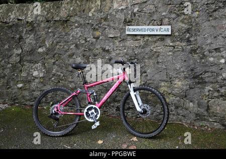 Bike left in Vicar's space. - Stock Photo