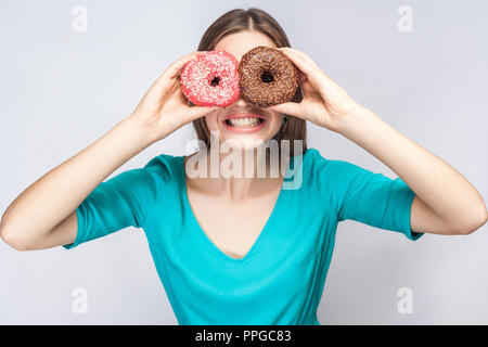 Positive young smiling girl in blue blouse standing, holding, covering eyes with pink and chocolate donuts,looking through donuts like making glasses  - Stock Photo