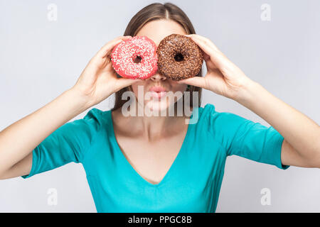 Positive young beautiful girl in blue blouse standing, holding, covering eyes with pink and chocolate donuts,looking through donuts like making glasse - Stock Photo