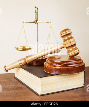 Law concept: wood gavel, soundblock, scales and volumetric old book are on light background - Stock Photo