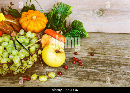 Green grapes in a basket and ripe apples, red cranberries, orange decorative pumpkin and squash with leaves on the wooden background with copy-space.  - Stock Photo