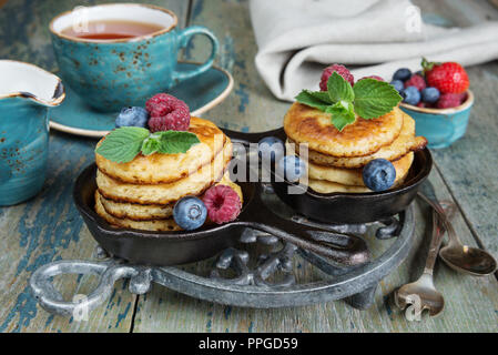 Breakfast of pancakes in cast-iron frying pans, fresh berries and black tea, in rustic style - Stock Photo