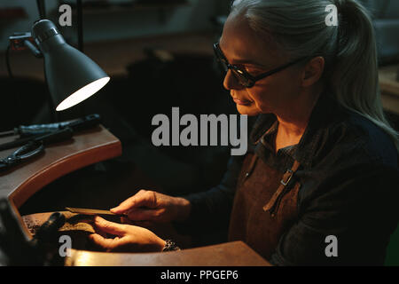 Goldsmith working and shaping an unfinished jewelry piece with a tool at a workbench in workshop. Mature female goldsmith working in her workshop. - Stock Photo