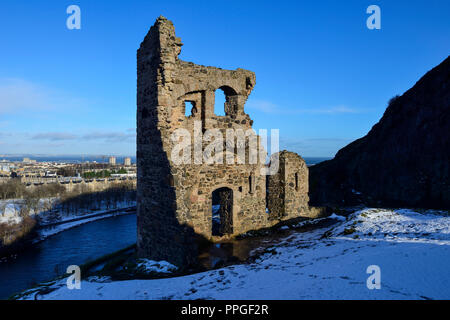 Ruins of St Anthony's Chapel in snow, with St Margaret's Loch in background, Holyrood Park, Edinburgh, Scotland - Stock Photo