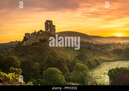 Corfe Castle, Dorset. 26th Sep 2018. UK Weather - After another cold night, a colourful sunrise over the historic ruins of Corfe Castle heralds the start to rising temperatures in the county of Dorset, England. Credit: Terry Mathews/Alamy Live News - Stock Photo