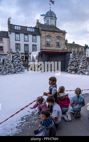 Kelso, UK. 26th September 2018. Children investigate artificial snowfall in Kelso, Scotland, town square after school on Wednesday September 26th 2018 - M&S Xmas TV advert being filmed in the town. Credit: David Kilpatrick/Alamy Live News - Stock Photo