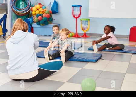 Group of kids is doing exercise to stretching in the gym in kindergarten or preschool - Stock Photo