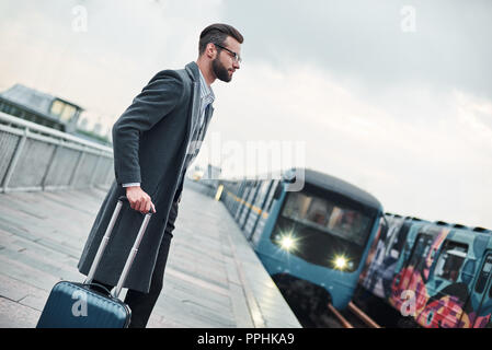 Business trip. Young businessman standing near railway with luggage waiting for train - Stock Photo