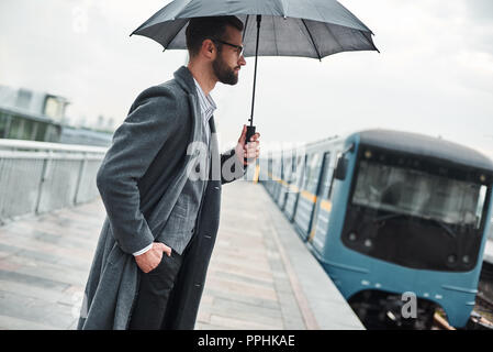 Waiting for train. Young businessman standing near railway under umbrella - Stock Photo