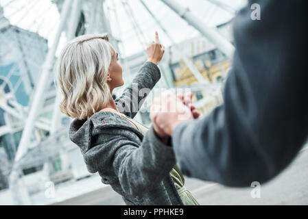 Romantic date outdoors. Young couple walking at entertainment park holding hands woman close-up pointing at ferris wheel excited - Stock Photo