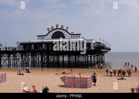 Papas fish and chip restaurant facade on Cleethorpes pier, tourists enjoying the beach in foreground. - Stock Photo