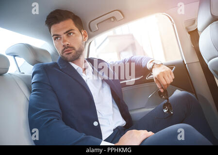 A young man is sitting in the backseat of cars and looks out the window. In his hands, sunglasses - Stock Photo