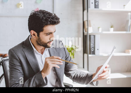 side view of handsome businessman reading documents and holding pencil in office - Stock Photo