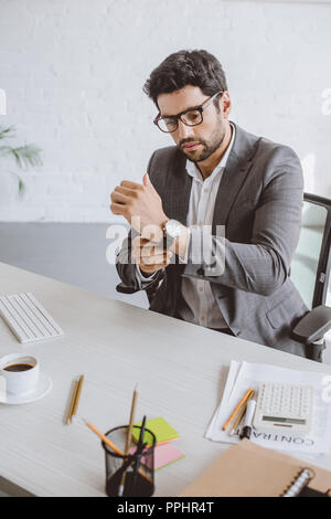 handsome businessman wearing wristwatch in office - Stock Photo