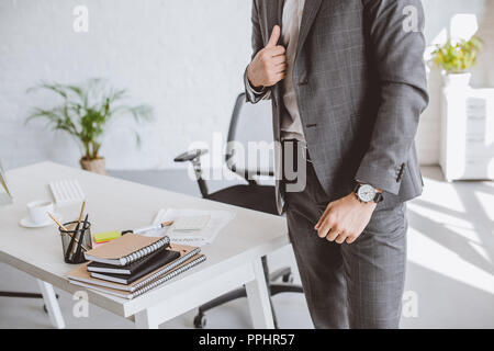cropped image of businessman standing in grey suit and with wristwatch in office - Stock Photo
