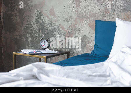messy bed in loft bedroom with vintage alarm clock and newspaper on bedside table - Stock Photo