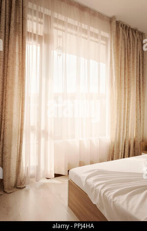 Hotel interior. Long beige curtains and tulle curtains, sheers on a window in the bedroom. Interior design concept. - Stock Photo