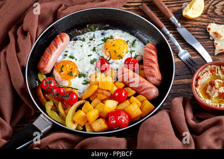 healthy breakfast set: maple glazed pumpkin, fried eggs with fresh parsley, roasted sausages, in a skillet with creamy baba ganoush sauce, pita, lemon - Stock Photo