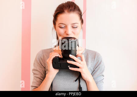 Pretty girl photographer kisses her camera and smiles - Stock Photo