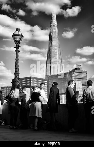 Office workers standing in front of Shard building chatting. - Stock Photo