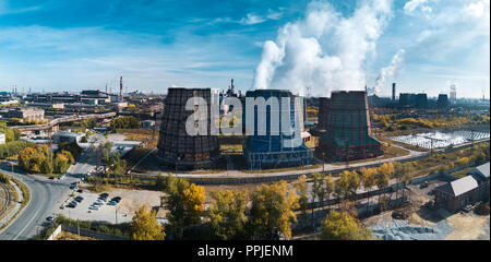 Concept of environmental pollution, drone view of smokestack pipe steel plant, aerial industrial panoramic landscape with blue sky and autumn vegetati - Stock Photo