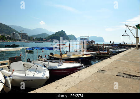 Small boat harbor with tourists and sightseeing boats in Petrovac, Montenegro, Europe. Beach with hotels in the background. Horizontal photo with copy - Stock Photo