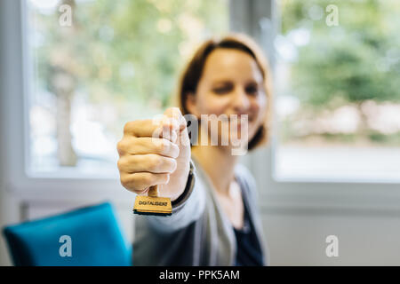 A woman in an office holds a wooden stamp with the german word 'digitalisiert' which means 'digitalized' into the camera, depth of field - Stock Photo