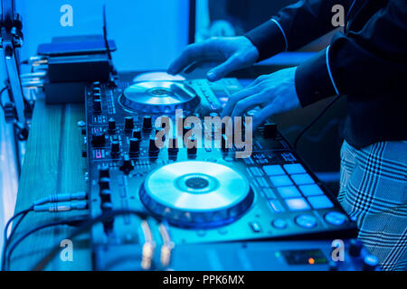 DJ plays and mix music on digital mixer controller. Close-up DJ performance controller, digital midi turntable system, adjustable torque, aluminum-turntable platter, fader, knob and slider, button. - Stock Photo