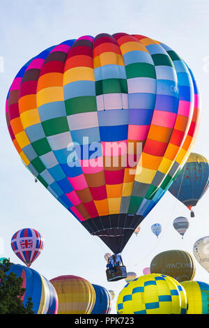 Hot air balloons rising for the mass morning ascent at Longleat Sky Safari, Wiltshire, UK in September - colourful balloons - Stock Photo