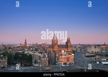 Skyline Amsterdam, Netherlands, in beautiful morning light with Saint Nicolas church. - Stock Photo
