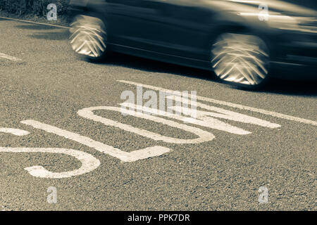 blurred car moving past road markings reading Slow - Stock Photo